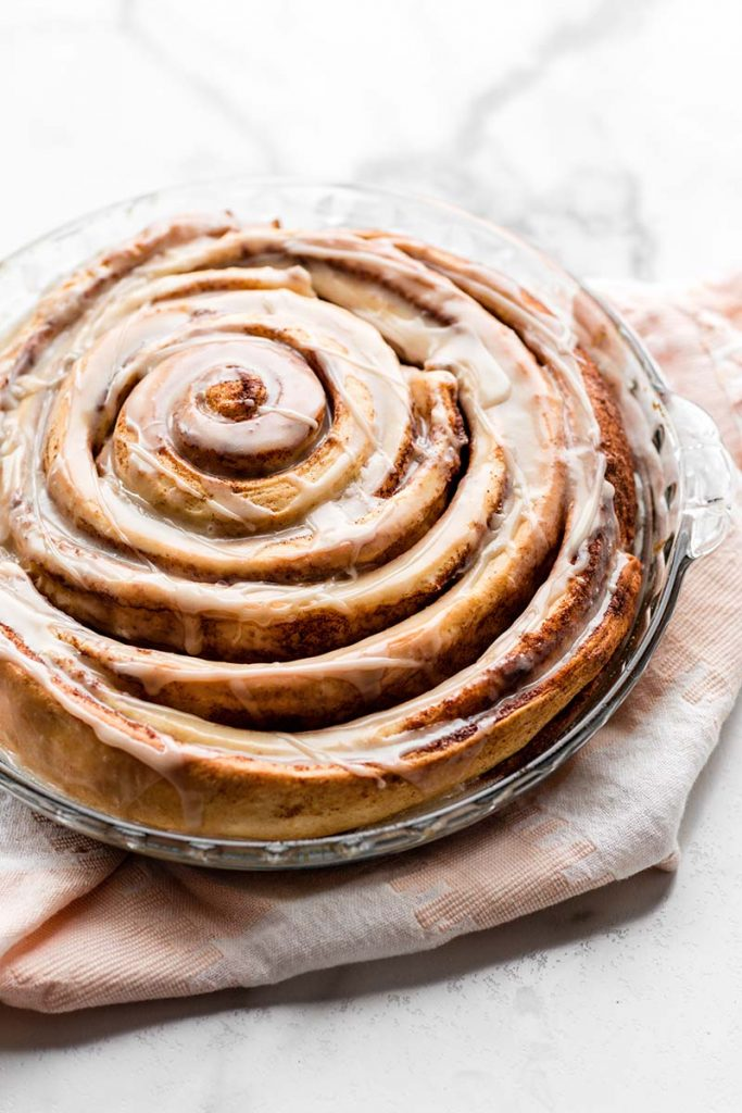 Giant Cinnamon Roll Cake | Learn how to make a giant cinnamon roll cake using my easy 7 ingredient homemade cinnamon roll dough and swirling it into one large cake. Top with vanilla icing for an extra indulgent breakfast or brunch. Kids and adults alike can't get enough and it's REALLY fun to make! Find recipe at redstaryeast.com.