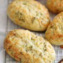 Asiago Herb Hoagie Rolls | Melted Asiago cheese and a garlic-herb butter topping make these soft and fluffy homemade hoagie rolls extra delicious as part of your favorite sandwiches. Find recipe at redstaryeast.com.