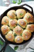Parmesan Pesto Skillet Rolls | These Parmesan pesto skillet rolls are soft, tender and fluffy, and filled and topped with cheese and pesto. They're perfect to bake and serve as a savory side dish or on their own! Find recipe at redstaryeast.com.