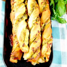 These Cheesy Pesto Breadsticks are soft and filled with delicious sweet basil pesto and ooey gooey cheese. They are guaranteed to steal the show at dinner! Find recipe at redstaryeast.com.