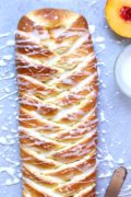 Peach Danish Braid | Filled with sweetened cream cheese and slices of sweet peaches, this peach Danish braid bakes up beautifully bronzed. Add a sweet almond drizzle for a scrumptious finish! Find recipe at redstaryeast.com.