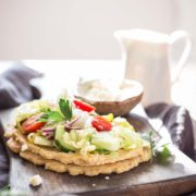 Gluten Free Greek Salad Naan Pizza | This homemade gluten-free naan bread is smeared with a thick layer of creamy hummus and topped with a heaping mound of Greek salad. Find recipe at redstaryeast.com.