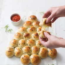 Herbed Fontina Rolls with Marinara Sauce | Perfect for sharing and packed with melty fontina cheese and a quartet of aromatic herbs, these yeasted potato rolls will chase away even the coldest of winter chills. Fluffy, buttery, and savory but with a touch of sweet from honey, they make for a fun appetizer or side for your holiday spread. Find recipe at redstaryeast.