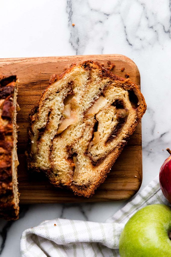 Apple Cinnamon Babka | Sweet apples and a thick cinnamon filling are twisted and swirled inside a rich and buttery yeasted babka dough. Finish this delicious apple cinnamon babka with a buttery brown sugar cinnamon crumble topping and bake until golden brown. Find recipe at redstaryeast.com.